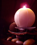 Candle. Over water that's falling on rocks Stock Photo