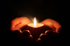 Candle. Hands holding one candle in darkness Royalty Free Stock Image