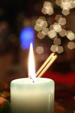 Candle. Lighted candle with many blured lights and spoon handle in the background. Picture taken during Christmas Eve Stock Images