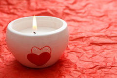 Candle. A burning white candle with hearts on it on the red background Royalty Free Stock Photos