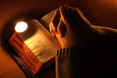 Candle. Arms crossed in prayer on the Bible Stock Photo