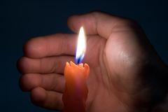 Candle. And hand in darkness stock photography
