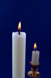 Candle. Two White candles burning against blue background Stock Photos
