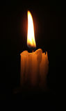 Candle. Glows from a seamless black background stock photos