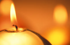 Candle. Close up of one glod candle in orange  and yellow background Stock Images