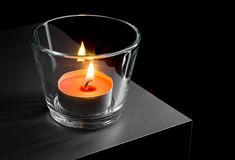Candle. Burning candle in glass on black background Stock Images