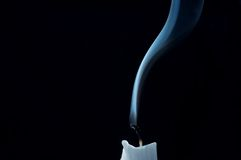 Candle. Extinguished in a draught on the black backdround stock photo