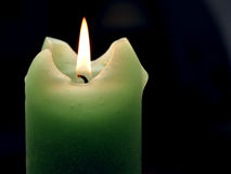 Candle. Green burning candle on the black background Stock Photos