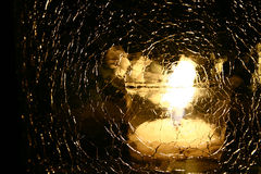 Candle. Light reflection through shattered glass royalty free stock photography