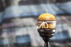 Candle. A yellow round candle on a stand Royalty Free Stock Photography