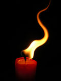 Candle. A burning red candle on black background Stock Images