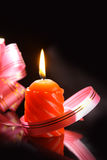 Candle. With ribbon on black background Stock Image