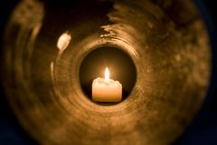 Candle. Ight at the end of the tunnel Stock Photo