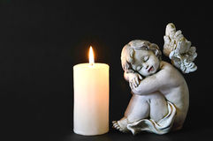 Candle and angel figurine Stock Photos