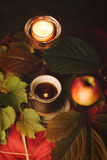 candle, apple and tea leaves near Stock Photos