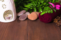 Candle in aroma lamp, stones and towel decorated with fern and p stock image