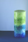 Candle. Aromatic pillar candle with light blue background Royalty Free Stock Photos