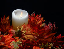Candle in Autumn Leaves. Lit candle in autumn leaves stock photo
