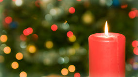 Candle on background of christmas tree Stock Photos
