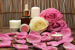 Candle on the background of natural cosmetics. Burning the candle on the background of natural cosmetics with roses and spices Stock Photography
