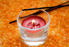 Candle in the background of an orange salt Royalty Free Stock Photography