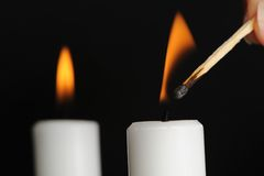 Candle Being Lit with Match. A candle being lit with a match with a burning candle in background Stock Photos