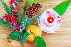 Candle, berries on pine brunch with tangerine Royalty Free Stock Images