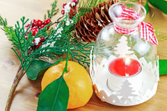 Candle, berries on pine brunch with tangerine Royalty Free Stock Photos