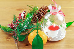 Candle, berries on pine brunch with tangerine Royalty Free Stock Photography