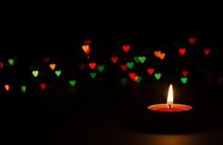 Candle on a black background with bokeh Stock Images