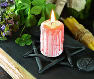 Candle on black magic book with clover. Burning candle with bloody drops on black book and with four leaf clover. Halloween filtered image Royalty Free Stock Photography