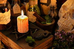 Candle on black magic book with skull and clover. Magic still life with burning candle and four leaf clover.  Halloween image. Signs on labels are not foreign Stock Images