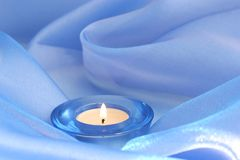 Candle on blue. Winter candle on blue swirly background Royalty Free Stock Images