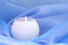 Candle on blue stock image
