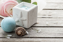 Candle and blue bath bomb over shabby wooden background Stock Photography