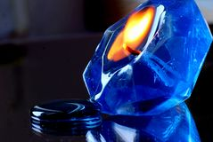 Candle. Blue burning  gem form gel candle on a mirror background with refflection Royalty Free Stock Images