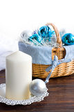 Candle and blue chistmas balls in basket on white Royalty Free Stock Images