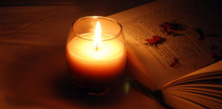 Candle Book. A worm mode with a candle placed beside a book Royalty Free Stock Photo