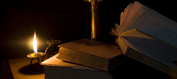 Candle and book. And black background Stock Photos