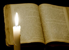 Candle and book Stock Images