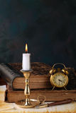 Candle with books. And an alarm clock stock images