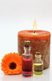 Candle with bottles containing oil. Spa like environment with candle, flower and two bottles containing aromatherapy oils Royalty Free Stock Photography