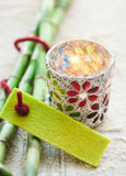 Candle burning alongside fresh green bamboo. Candle burning in a decorative container alongside fresh green bamboo with an attached green textile tag with fiber Royalty Free Stock Image