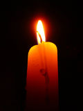 Candle burning with a beautiful flame. Wax candle burning with a beautiful flame on a black background royalty free stock photo