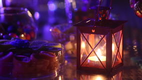 Candle burning in a candlestick near a variety of sweets stock footage