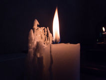 Candle burning in the dark Stock Images