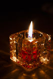 Candle burning in the dark in glass holder on black background, stock photos