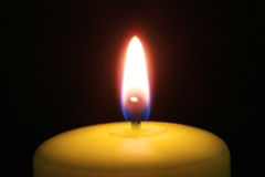 Candle burning in darkness. Close up of single candle burning in darkness Royalty Free Stock Photo
