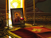 A candle burning in front of an icon. Of holy mother and child royalty free stock photography