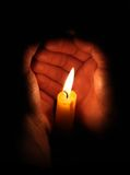 Candle burning in hands Stock Image